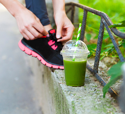 Green detox smoothie cup and woman lacing running shoes